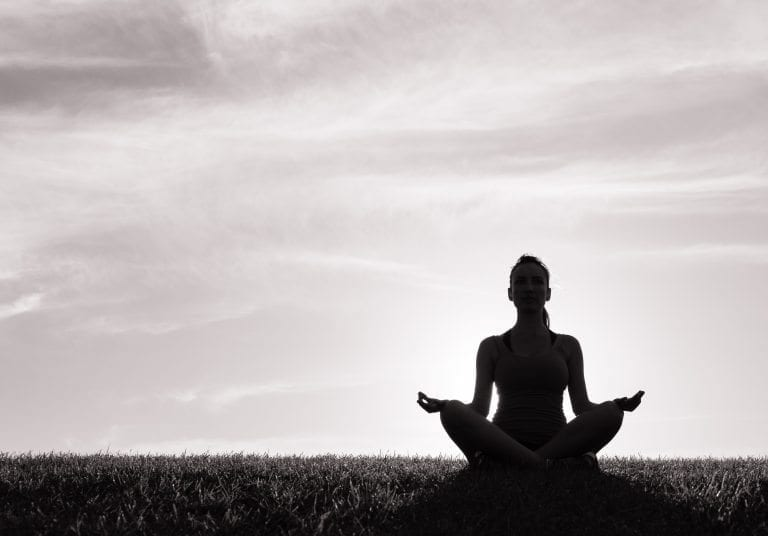 Woman meditating in yoga pose outdoor.
